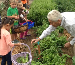Gachina Landscape Management recently converted 5,000 square feet of their construction yard into an organic vegetable garden that was awarded a Certified Wildlife Habitat™ designation by the National Wildlife Federation. Here, company president, CEO and founder John Gachina works with children in the demonstration garden.